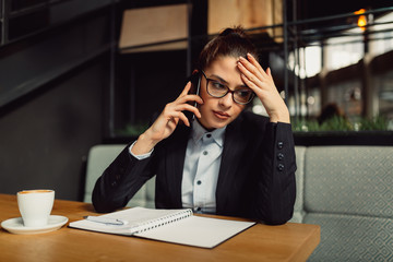 Worried businesswoman with eyeglasses holding smart phone, taking notes. Girl in cafe holding hand on forehead. Business, online business, remote office concept.