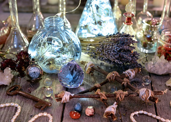 Magic bottles with lights, pentagram, crystal and ritual objects on witch table. Occult, esoteric, divination and wicca concept. Halloween background with vintage objects