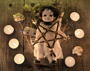 Scary voodoo doll with candles, pentagram and poison berries on witch table. Occult, esoteric, divination and wicca concept. Halloween background with vintage objects