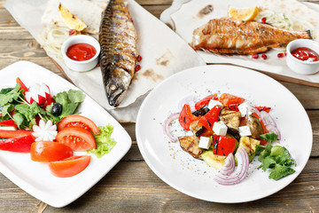 grilled mackerel and sea bass. Salad of fresh vegetables. Serving on a wooden Board on a rustic table. Barbecue restaurant menu, a series of photos of different meats anf fish