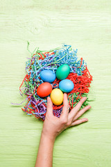 Photo of multicolored easter eggs and hand on green wooden background