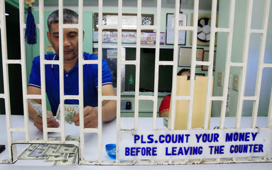 A worker counts U.S. dollar bills inside a money changer in Metro Manila