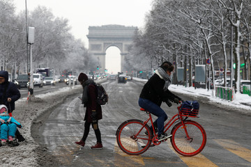 A man rides a bike on the Champs Elysees avenue with the Arc de Triomphe in the background in Paris, as winter weather with snow and freezing temperatures arrive in France