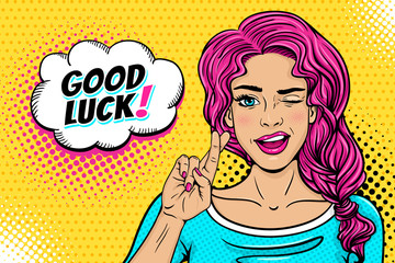 Pop art female face. Sexy young woman winks with pink hair and open smile, crossed fingers for luck symbol and Good Luck speech bubble on halftone. Vector colorful illustration in retro comic style.
