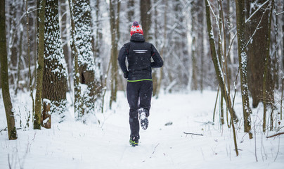 Image from back of running athlete among trees in winter forest