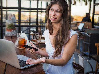 busy digital nomad woman with laptop and phone in a cafe