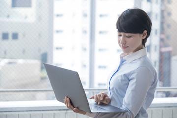 ノートパソコンを持つ女性
