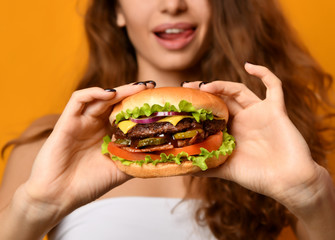 Woman eat burger sandwich with hungry mouth on yellow background