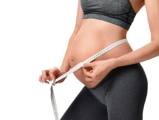 pregnant woman measure big belly with tape measure