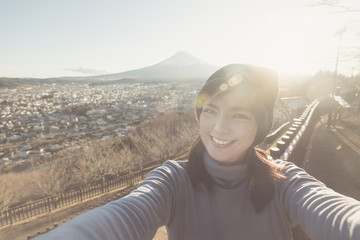 Portrait of Attractive asian woman making selfie photo with moutain Fuji background on sunset