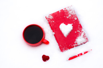 Red cup of coffee or tea with a red book or notebook or photo albums with heart. Snow is coming. Winter concept of Valentine's Day