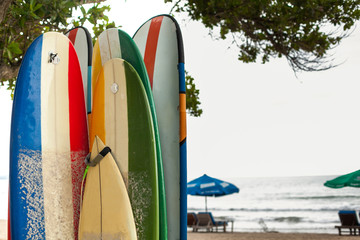Set of different color surf boards in a stack by ocean.Bali.Indonesia. Surf boards on sandy beach. Vintage