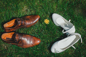 Vintage grooms leather shoes with white bridal high heel on the bright green grass. Rustic photo and rural view. yellow summer dandelion. Wedding details.