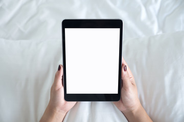 Top view mockup image of a woman holding black tablet pc with blank desktop white screen while sitting on a white bed background