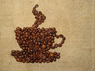 Coffee сup made of roasted coffee beans on burlap