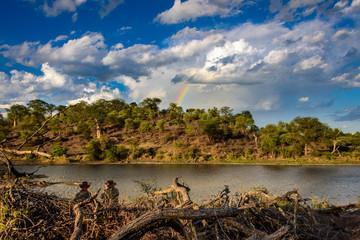 Personen am Wasser im Sonnenuntergang mit Regenbogen und spektakulären Wolken am Himmel