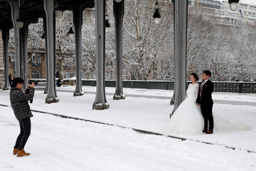 A wedding couple of tourists pose for their own photographer on the snow-covered Pont de Bir-Hakeim bridge as winter conditions with snow and freezing temperatures hit in Paris