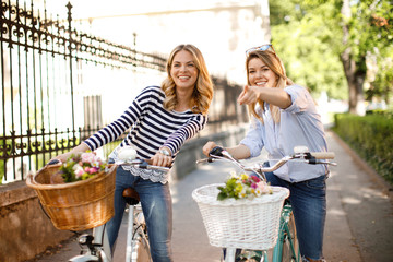 Two young women tourists exploring the city on bicycles
