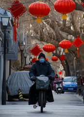 A man rides an electric bicycle through a hutong alley decorated with Spring Festival lanterns in an old neighbourhood of Beijing ahead of the Chinese Lunar New Year,
