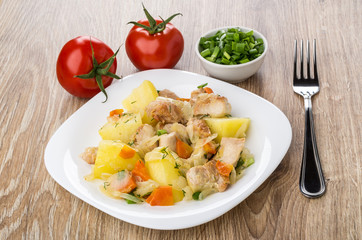 Meat with potatoes, carrot and onion, bowls with scallion, tomatoes