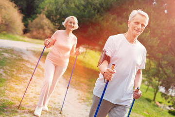 Great mood. Optimistic elderly family walking through the forest while using crutches and having cheerful mood