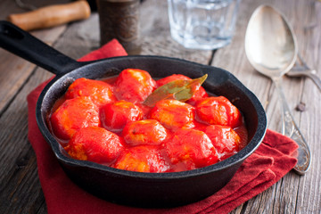 Meatballs in tomato sauce in a cast-iron frying pan on a wooden table, horizontal
