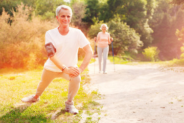 Cheerful emotions. Full length of positive man expressing optimism while doing exercises in fresh air and caring about his health