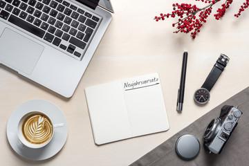 Neujahrsvorsatz auf Notizblock auf Fotografen Schreibtisch von oben