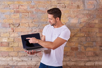 A serious handsome young man holding a laptop PC and pointing to the screen in a white tshirt.