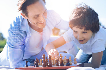 He is so smart. Satisfied adult man beaming while looking at his little son playing chess and really enjoying the process during a family walk session.