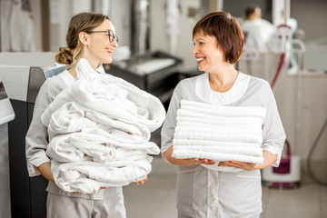 Senior chambermaid with young assistant standing with clean bedclothes and bathrobes in the hotel laundry