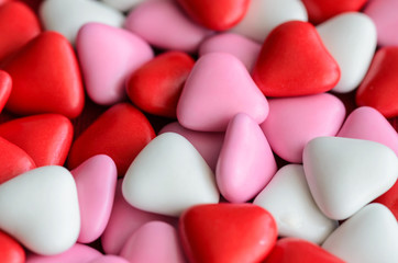 White, pink and red heart shape candies background for Saint Valentines Day or Love concept.