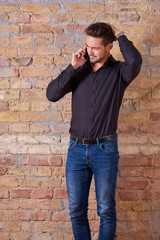 A worried handsome young businessman talking on his phone in a black shirt.