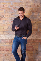 A serious handsome young businessman using his smartphone in a black shirt.