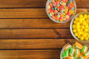 Brightly colored candies in glass cups on a wooden table, top view, free space for text