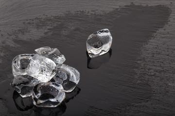 Large ice cubes on black slate board