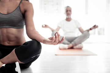 Everything will be good. Selective focus on a sporty lady wearing sportswear sitting in a lotus position and meditating during a yoga class.