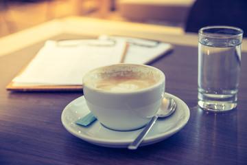 Kaffeetasse mit Wasserglas auf Holztisch. Konzept.