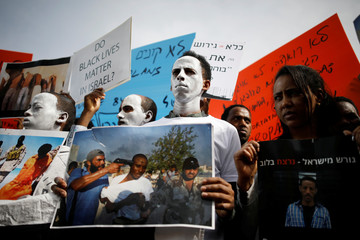 African migrants painted in white hold signs during a protest against the Israeli government's plan to deport part of their community, in front of the Rwandan embassy in Herzliya