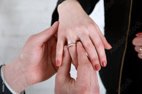 grooms hand putting a wedding ring on the brides fingerWedding