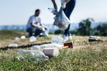 Environmental pollution. Selective focus of litter lying on the grass in the park