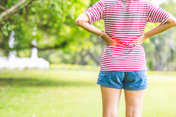 Woman Back Pain on Natural Outdoor Background / Healthcare and Medical