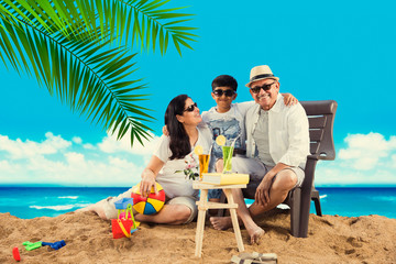 Indian grandparents at beach with grand child, having fun while clicking selfie picture, playing in sand and looking at camera