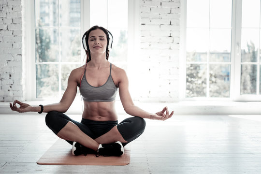 After stressful day. Joyful woman smiling while listening to music and sitting in a lotus pose during a meditation session.