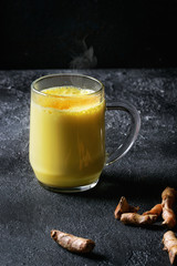 Cup of ayurvedic drink golden milk turmeric latte with curcuma powder and ingredients above over black texture background.