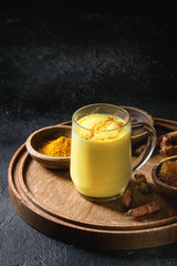 Cup of ayurvedic drink golden milk turmeric latte with curcuma powder on round wooden tray and ingredients above over black texture background. Copy space