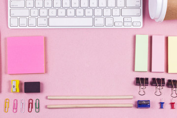 Content of student's bag. Keyboard, notebook, stationery, coffee cup on pink background top view copy space