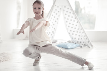 Exercising. Beautiful happy vigorous long-haired girl smiling and doing some exercises in her room while wearing white t-shirt and trousers