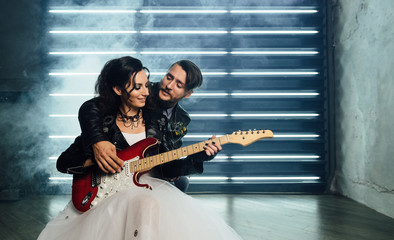 Wedding in the style of rock. Rocker or Biker wedding. Guys with stylish leather jackets. It's a rock'n'roll baby! Sweet couple in a photo studio. Steep shooting with electric guitar and smoke.