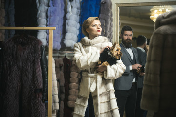 Woman in fur coat with man, shopping, seller and customer.